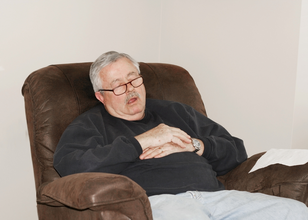 man sleeping in recliner chair
